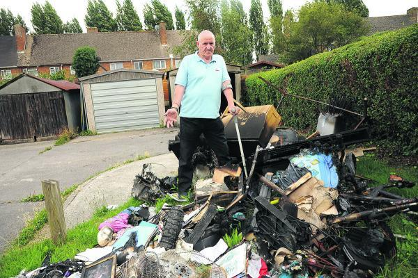 This Is Wiltshire: James Burrell with the burnt remains of the contents of his garage