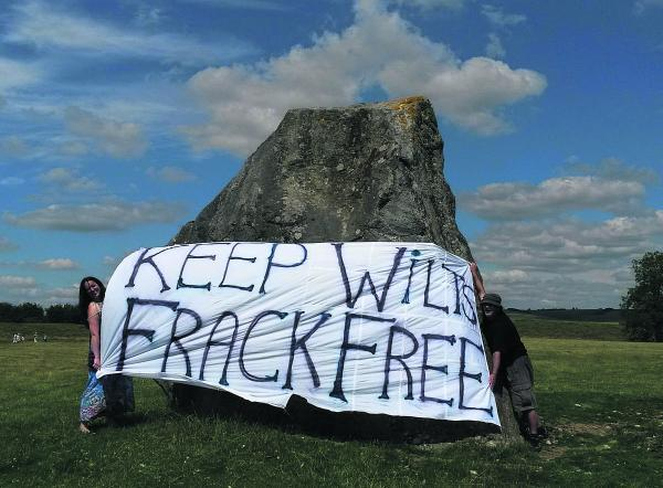 This Is Wiltshire: Anti-fracking campaigners Becky Martin and Clive Humphries unveil a banner at Avebury