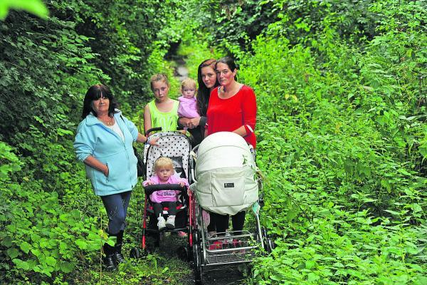This Is Wiltshire: Cilla Mountstephens, left, with members of her family on the  footpath which leads to Warminster Cemetery where she has six graves she tends