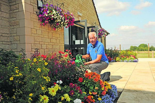 This Is Wiltshire: Ian Lawes tending to the floral display at the Trowbridge Rugby Club