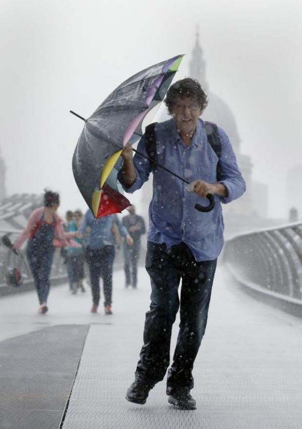 This Is Wiltshire: A pedestrian stuggles against the wind and rain in London today