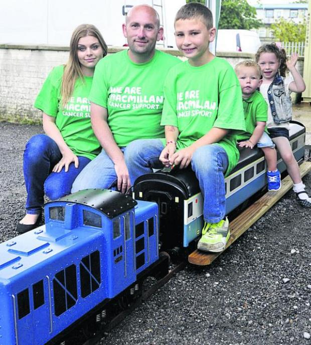 This Is Wiltshire: Naomi Jordan, Jason Pym, driver Samuel Pym, aged 10, and pasengers Koel Vowles and Sienna Jones on the Pyms' 0-6-0 gauge electric model diesel engine at summer fete at Westbury in aid of Macmillan Cancer Support. Picture by Glenn Phillips