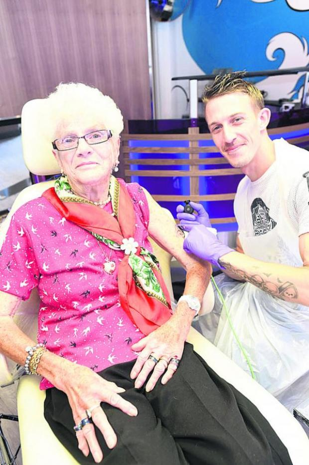 This Is Wiltshire: Doreen Avery, 80, has a seahorse tattoo done at Tom Swift's new shop in Devizes                     (DV1512) By Diane Vose