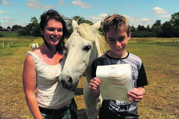 This Is Wiltshire: Alison Smith, of Wiltshire Equine Assisted Learning, presents the grooming qualification to 14-year-old Luke McGlinchey with George the horse. (TP50099) By Trevor Porter