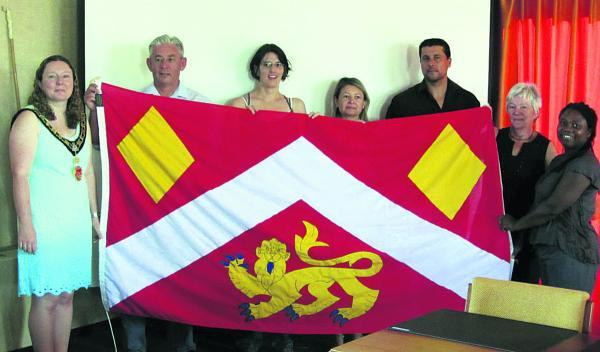 This Is Wiltshire: Royal Wootton Bassett mayor Sue Hughes, who is twinning association vice-chairman, presents a large Royal Wootton Bassett flag that bears the new town crest to the mayor of Blain