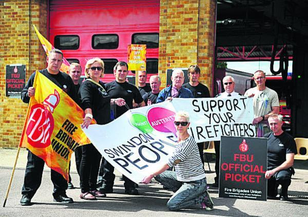 This Is Wiltshire: Kate Linnegar of Swindon People's Assembly, front, with picketing firefighters at Drove Road Fire Station yesterday