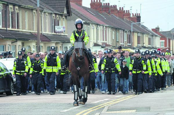 This Is Wiltshire: Police escort visiting fans into the County Ground before a match