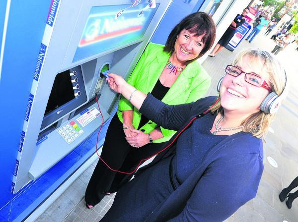 This Is Wiltshire: Customer experience directorJenny Groves shows reporter  Liz Mackley how to use Nationwide's new cash machine in Regent Street