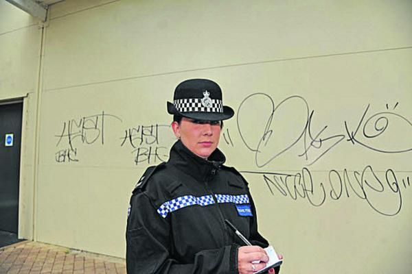 This Is Wiltshire: PC Charlotte Chilton with graffiti on a wall at Sainsbury's, Trowbridge     Photo: Trevor Porter