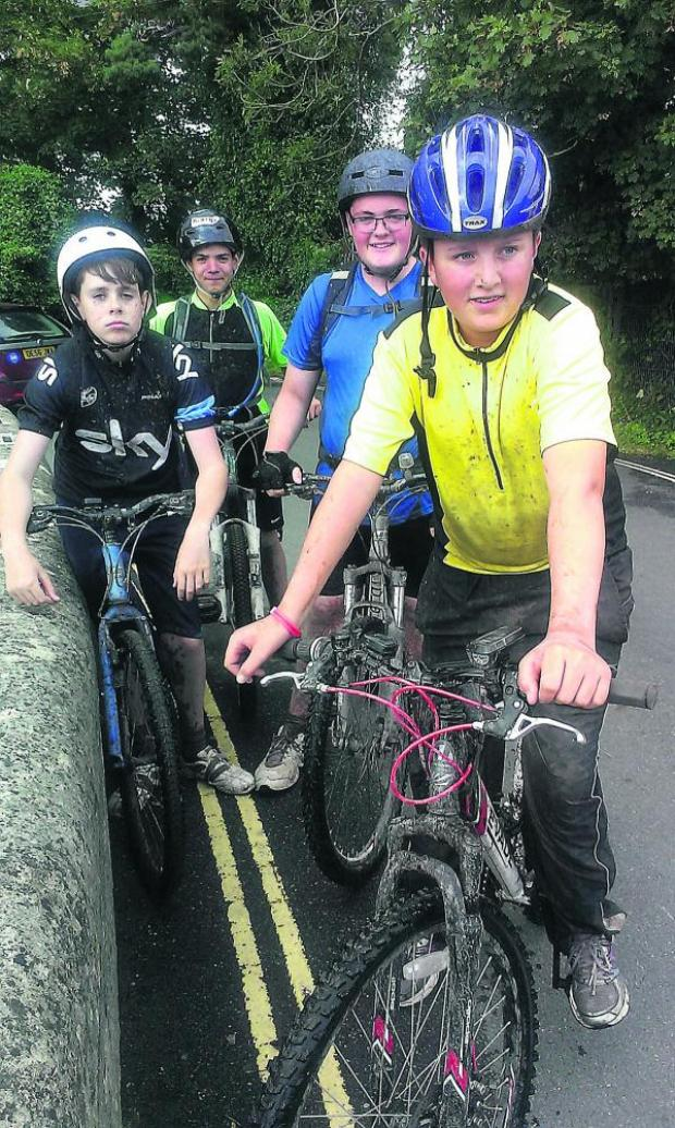 This Is Wiltshire: Pictured at the end of their charity ride are Jack Colyer (front in yellow T-shirt), Conor Dunne (blue T-shirt), Liam O'Donnell (Sky T-shirt) and Kofi Pegden at back