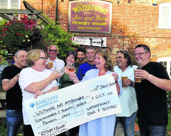 This Is Wiltshire: Volunteer Tracey Pullen, front left, receives the cheque from co-owners Nicky Rouse, Nigel Wallace and chef Carl Games. Other fundraisers are, from back left, Frank Day, Richard Stawt, Liz Boden, Wayne Richards and Nick Clark      (SMB050/1) By Siobhan Bo
