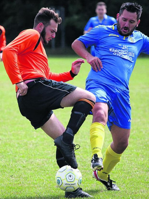 This Is Wiltshire: Woottton Bassett Town Development's Rich Clark (right) challenges Trowbridge Wanderers' Jordan Pinder las