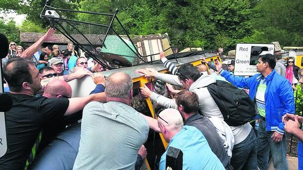 This Is Wiltshire: Onlookers rush to help as the Longleat train topples over. Three people were hurt, one seriously, in Wednesday's accident     Photo by Lisa Mowe