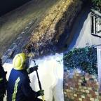 This Is Wiltshire: Firefighters inspect a thatched roof following four house fires near Cambridgeshire (Cambridgeshire Fire and Rescue Service/PA)