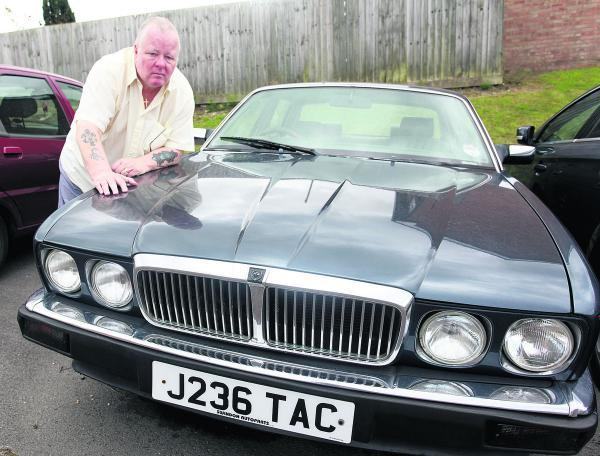 This Is Wiltshire: Pat Willis with his Jaguar which he claims was damaged after council workmen cut the grass and stones chipped it