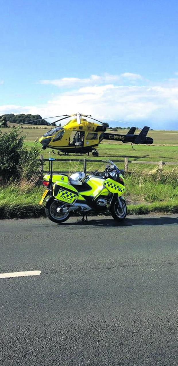 This Is Wiltshire: The air ambulance lands on the field next to the accident