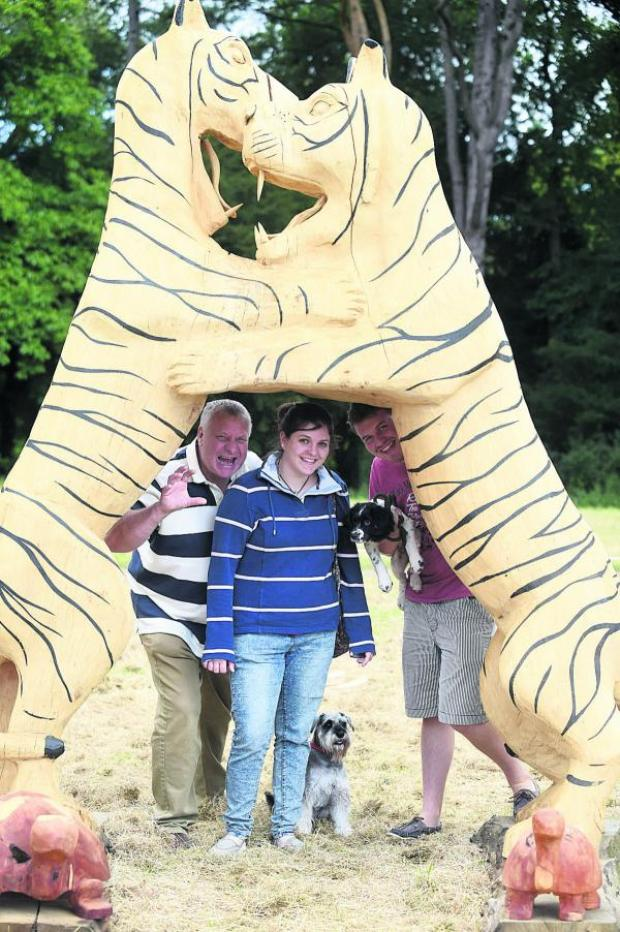 This Is Wiltshire: Paul, Amy and Sam Middleton with their dogs Bo and Alfie admire a wood carving by Steve Griffin at Treefest