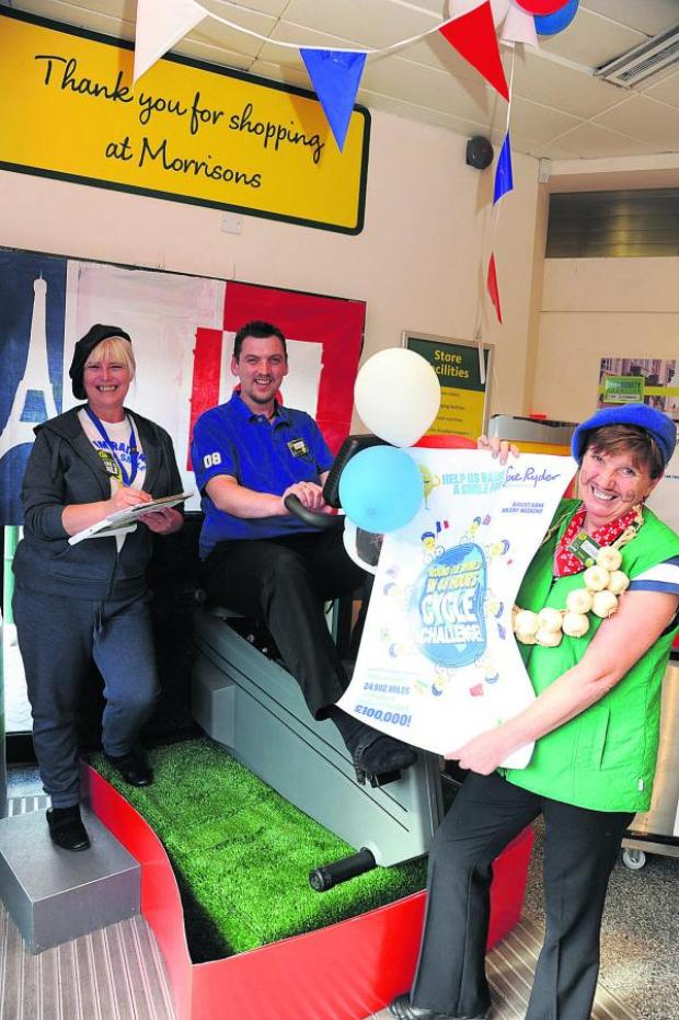 This Is Wiltshire: Morrisons staff members Barbara Webber and Lorraine Lewis dressed in French attire as administration  manager Gareth Wellbelove pedals towards the 223 mile goal
