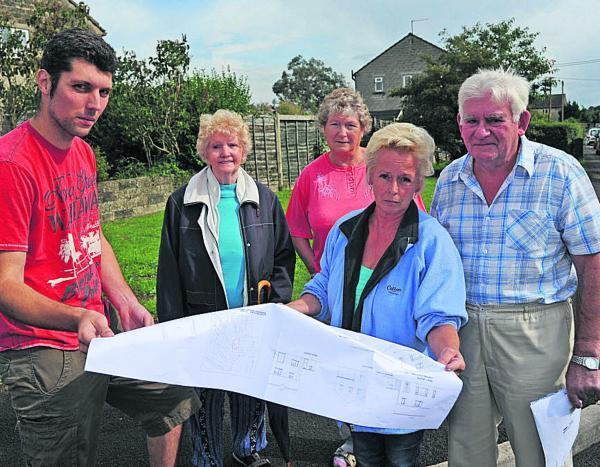 This Is Wiltshire: Lee Davis and Shirley Sloper hold plans for the two homes planned along with fellow Marshmead residents angry at the proposal. Picture by Trevor Porter