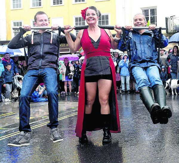 This Is Wiltshire: Strong woman Betty gives Matt Goddard and Brandon Wellard a twirl at Devizes International Street Festival. Picture by Diane Vose