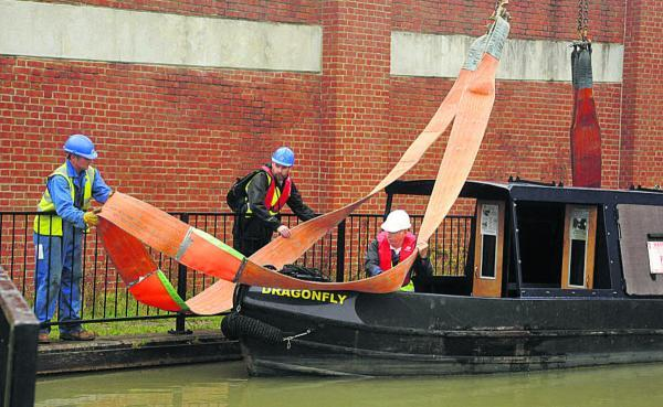 This Is Wiltshire: The Wilts and Berks Canal Trust's Dragonfly is lifted from the water for its trip to Melksham