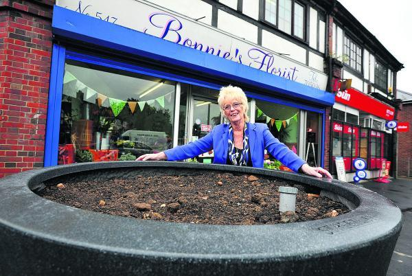 This Is Wiltshire: Bonnie Bull, the owner of Bonnie's Florist, in Pinehurst, is pleased with the new giant pots the council has placed outside the shop
