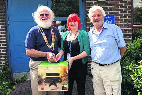 This Is Wiltshire: Devizes Rotary Club president Tom MacMeekin, left, and past president Geoff Collins present the Xbox to Green Lane Hospital ward manager Hannah MacDonald