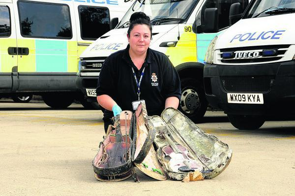 This Is Wiltshire: Property officer Louise Earle with the stolen violins at Melksham Police Station              (PM1441)