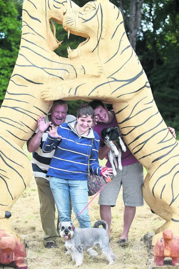 This Is Wiltshire: Paul, Amy and Sam Middleton with dogs Bo and Alfie under the two tigers woodcarving by Steve Griffin