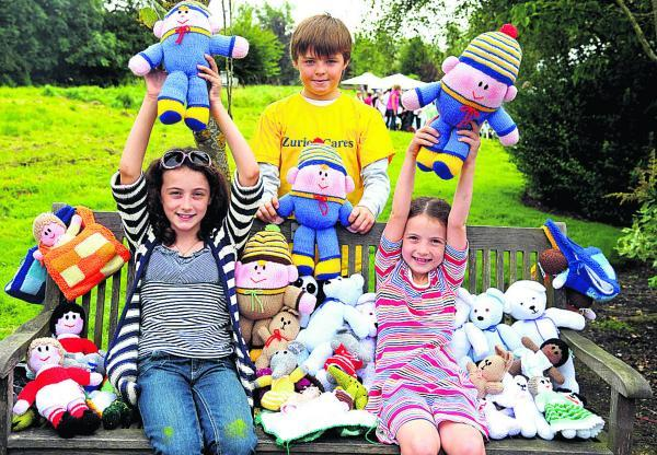 This Is Wiltshire: Having a great time with their knitted friends at a previous Prospect Hospice summer fete are, left to right, Millie Anderson, Oliver Shimell and Isabel Anderson