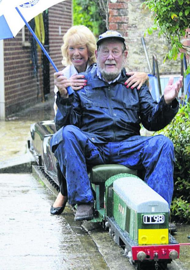This Is Wiltshire: Nev Boulton and his wife Thelma brave the rain on Bank Holiday Monday at Great Bulkington Railway