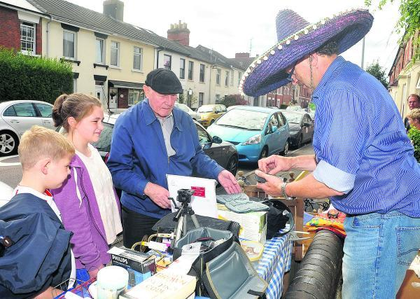 This Is Wiltshire: Robert Wakefield, right, selling a few of his belongings at the Old Town yard sale. Picture: Vicky Scipio