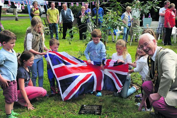 This Is Wiltshire: Children from Clarendon Avenue help Trowbridge Mayor Cllr Glyn Bridges unveil the WWI plaque on the green. Picture by Trevor Porter
