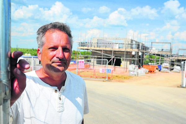This Is Wiltshire: Kevin Fisher, chair of Shaw residents association at the Ridgeway Farm construction site. Concerns have been raised about the design of the main road serving the development