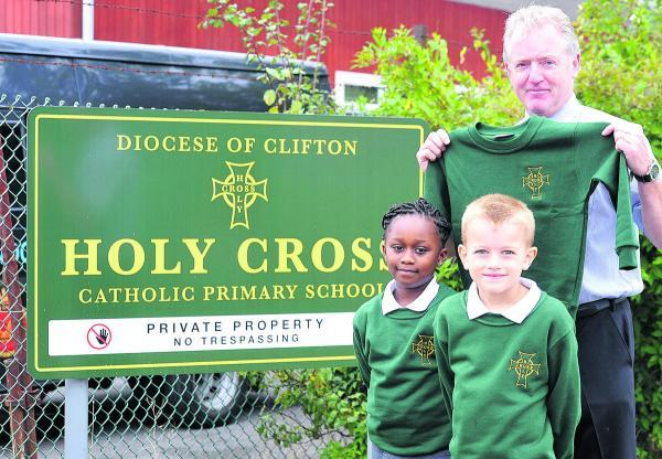 This Is Wiltshire: Holy Cross Catholic Primary School which has new uniforms to go with the name. From left, pupils Beatrix and Adam with head teacher Tony McAteer