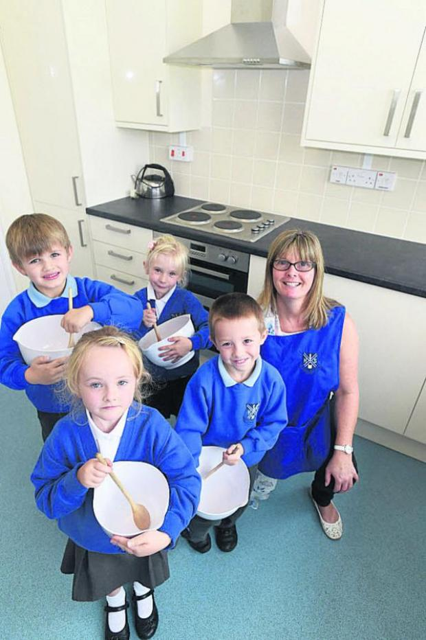 This Is Wiltshire: Heddington pupils pick up some cooking tips in the new kitchen at the village hall next to their school