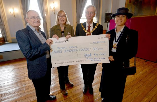 This Is Wiltshire: Devizes Food and Drink Festival treasurer Dave Mitchell and chairman Philippa Morgan present a cheque to Devizes Mayor Roger Giraud-Saunders who is accompanied by his wife Giovanna