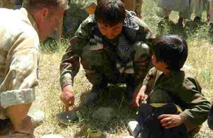 A Sapper from 26 Engineer Regiment (left) and an Afghani soldier point out the dangers of mines to an Afghani youngster during a landmine awareness campaign in Helmand Province.