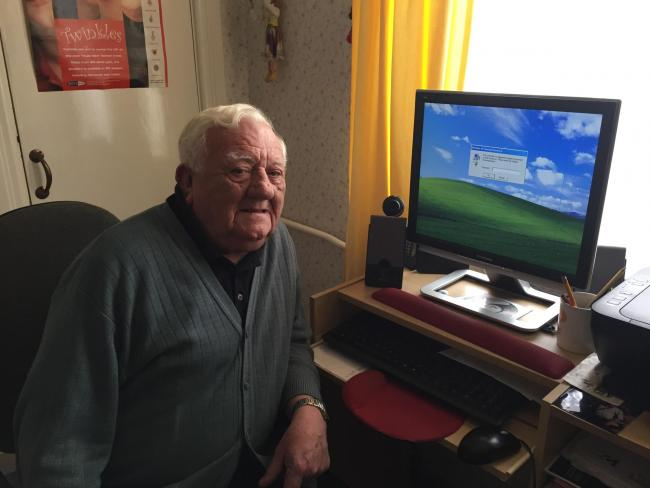 Eric Sutton in front of his computer, now unuseable after it was blocked by conmen. (57878843)