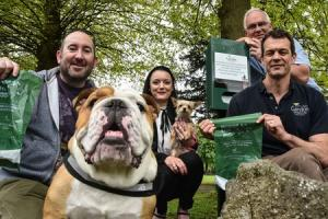 Vet Nick Hill (seated right) from sponsors Garston Vets with Bill Austin from Trowbridge Town council , dog owners Aby Cooper with her dog Berti  and Alan Paterson with Hamish the bulldog taking a look at one of the 4  new dog poo bag dispensers in Trowbr