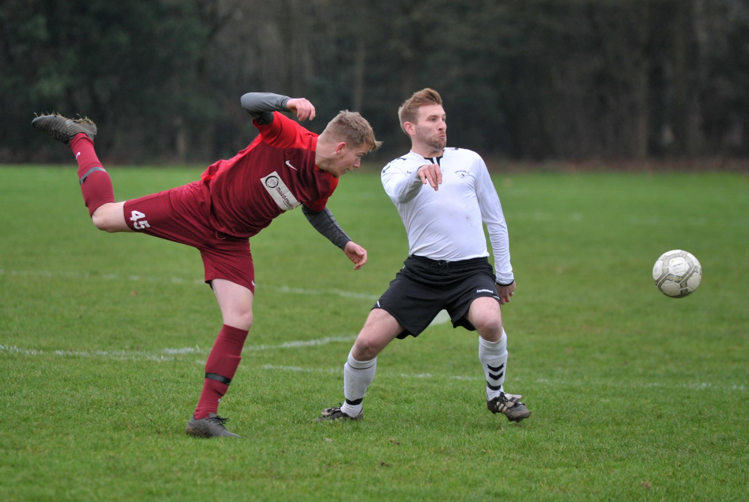 FC Walcot's Alex Hammond (red) and Greyhound player Glenn Armstrong in action during the two sides' 1-1 Premier Division draw in the Swindon Sunday League       Picture: DAVE COX