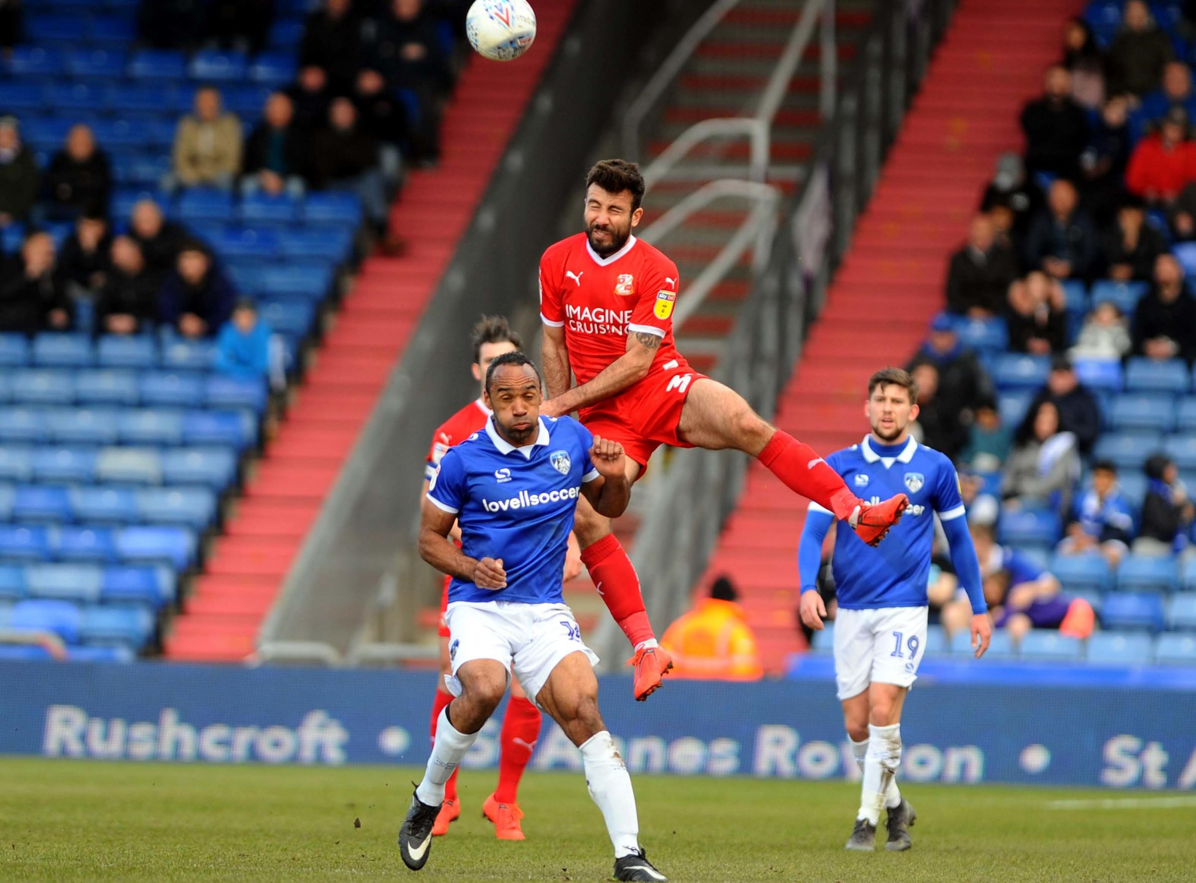 Michael Doughty, who scored Swindon Town's first goal on the day, climbs to win a high ball during Saturday's draw at Oldham Athletic