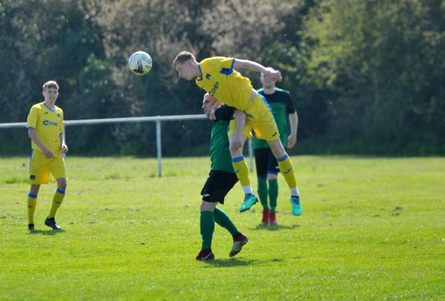 Football ID's Harrison Lea (yellow) wins a high ball during his side's 3-2 defeat against Cricklade Town                 Picture: DAVE COX